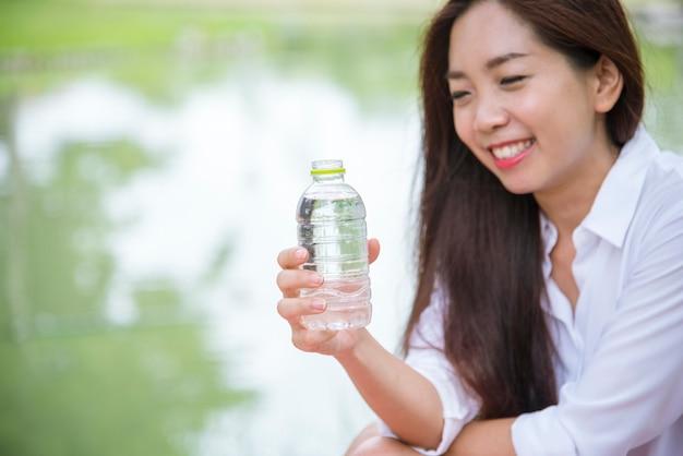 행복 미네랄 워터 병을 들고 행복하고 웃는 아름다운 아시아 중국 여성