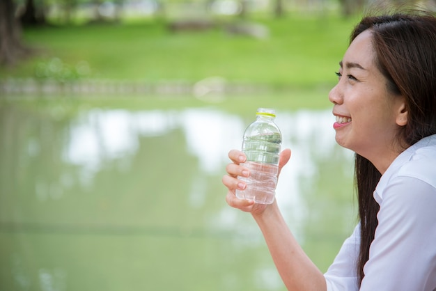 Happiness beautiful asian chinese women holding mineral water bottle happy and smiling