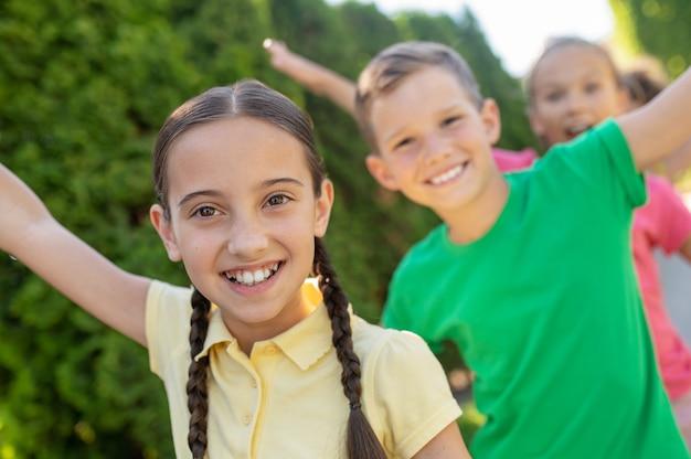 행복. 아름다운 웃는 소녀들과 소년들은 활기차게 노는 여름날 야외에서 함께 즐거운 시간을 보낸다