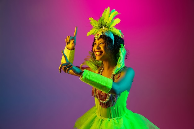 Happiness. beautiful young woman in carnival, stylish masquerade costume with feathers dancing on gradient background in neon. concept of holidays celebration, festive time, dance, party, having fun.