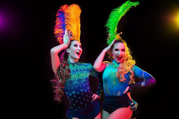 Happiness. beautiful young women in carnival, stylish masquerade costume with feathers on black background in neon light. copyspace for ad. holidays celebration, dancing, fashion. festive time, party.