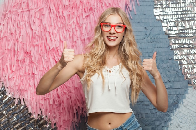Happiness blonde girl in red glasses showing thumbs up looking at camera and smiling