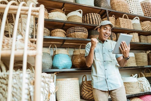 幸福のビジネスオーナーは、棚に工芸品がある工芸品店でタブレットを使用します