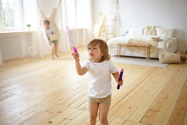 Happiness and carefree childhood concept. indoor portrait of adorable happy female child in t-shirt and shorts standing in the middle of modern living room, having fun, blowing soap bubbles,