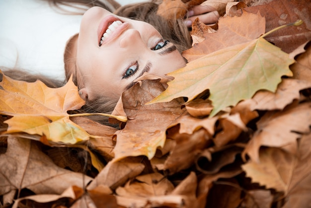 Happiness carefree happy autumn beautiful girl lies in maple yellow leaves