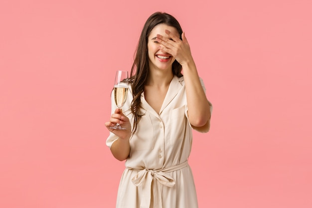 Happiness, celebration and party concept. carefree romantic and delighted caucasian female in luxurious dress, laughing cover face as hearing hilarious joke, have fun, raising glass champagne