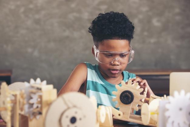 モデルの一部を探している安全メガネを身に着けている幸福陽気な子巻き毛黒髪賢い