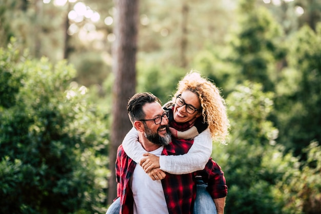 Happiness and cheerful people concpet with joyful couple playing and having fun together in the wood country side - adult man and woman in relationship carrying and laughing a lot together outdoor