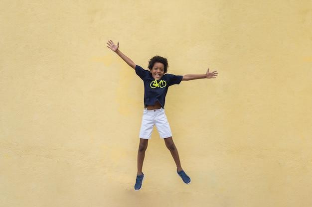 Счастье, детство, свобода, движение и люди концепции - счастливый улыбающийся мальчик прыгает в воздухе