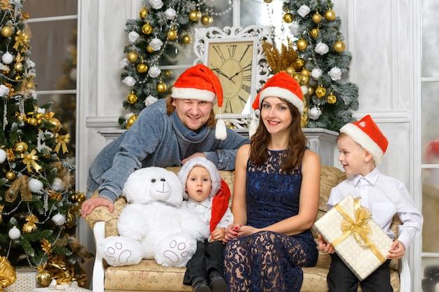 幸せのクリスマスのコンセプト-多くのギフトボックスとサンタヘルパー帽子で笑顔の家族