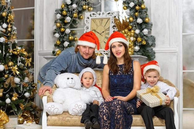 幸せのクリスマス家族の概念-サンタの帽子とギフトボックスの家族