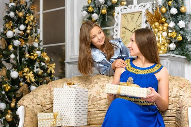 幸せのクリスマスの家族の概念-ギフトボックスと娘を持つ母