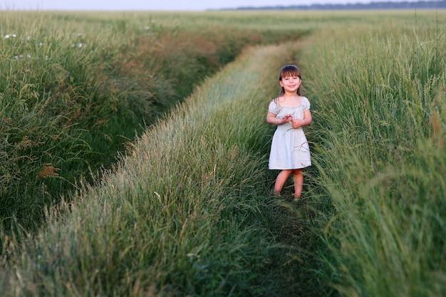 緑のフィールドの近くの幸せの概念の小さな幸せな女の子