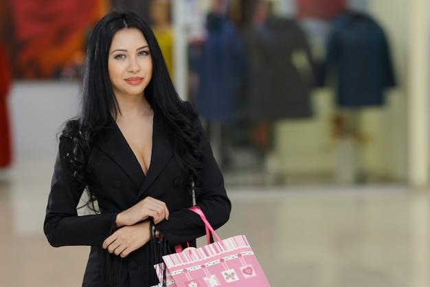 幸福、消費主義、販売、人々のコンセプト-モールの背景に買い物袋を持って笑顔の若い女性。コピースペース