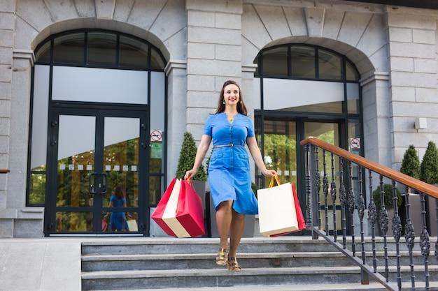행복, 소비, 판매 및 사람들 개념. 쇼핑백과 젊은 여자를 웃 고