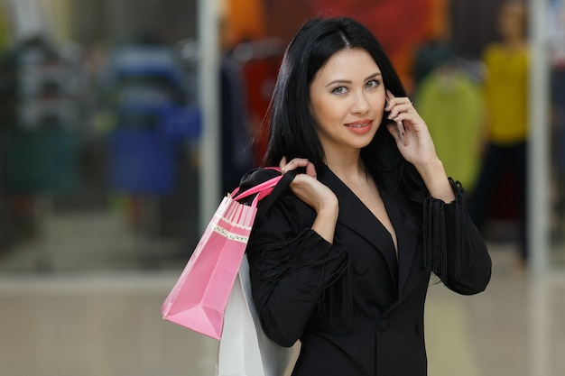 幸福、消費主義、販売、人々の概念-ショッピングバッグを持って、モールで携帯電話で話している若い女性