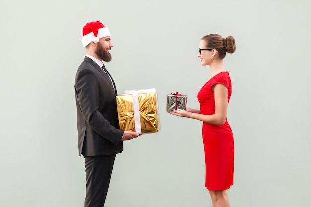 Пара счастья смотрит друг на друга и держит подарочную коробку. студийный снимок. серая стена