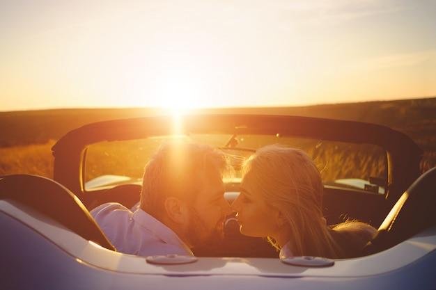 幸せなカップルが新しいスポーツカーにとどまる