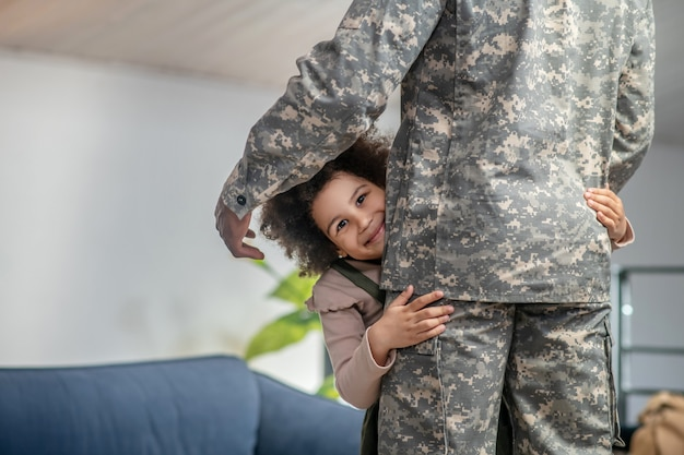 Happiness. cute happy little girl with dark curly hair hugging dad in military uniform standing at home in room