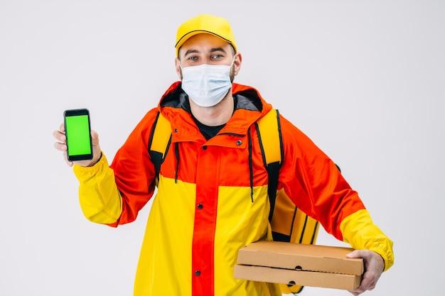 Доставщик счастья держит пиццу, показывая зеленый экран своего смартфона, отдавая приказ в маске во время пандемии covid19 в студии на белой поверхности