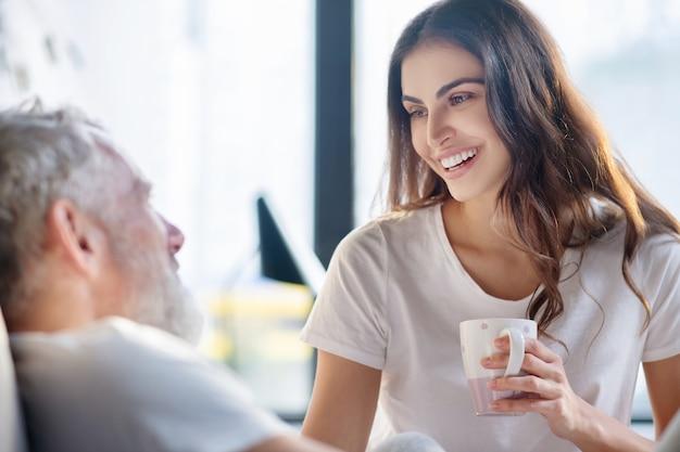 Счастье, эмоции. крупным планом счастливой длинноволосой женщины с белой зубастой улыбкой с чашкой кофе и мужчиной