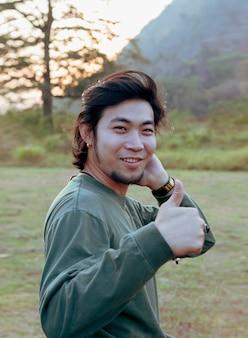 Лицо счастья азиатского молодого человека, стоящего на открытом воздухе