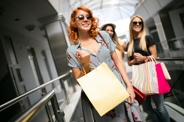 幸せ、友達、買い物、そして楽しいコンセプト-買い物袋を持った若い女性の笑顔。