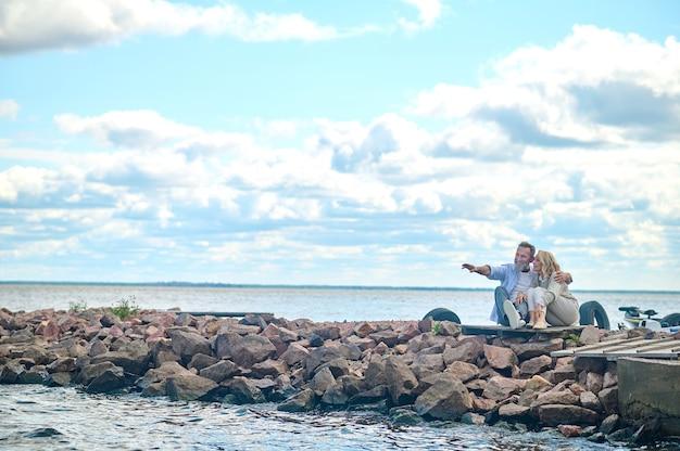 행복. 행복한 성인 여성과 포옹하는 남자가 바다 옆에 앉아 휴식을 취하고 있는 거리에 재미있는 것을 손으로 보여줍니다.