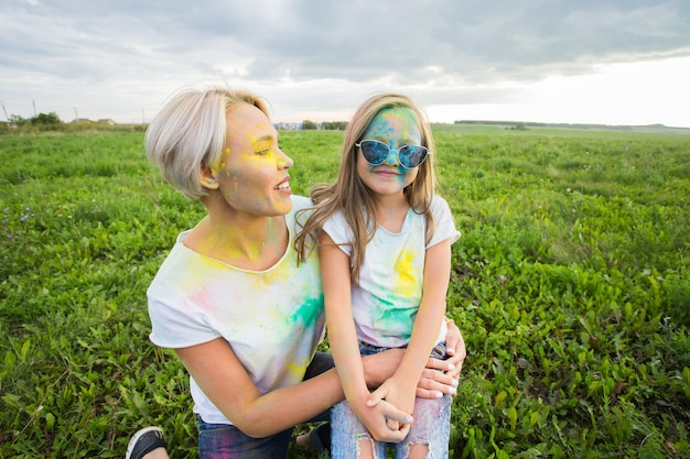 幸福、ホーリー祭、休日のコンセプト-母と娘はカラーパウダーで覆われています