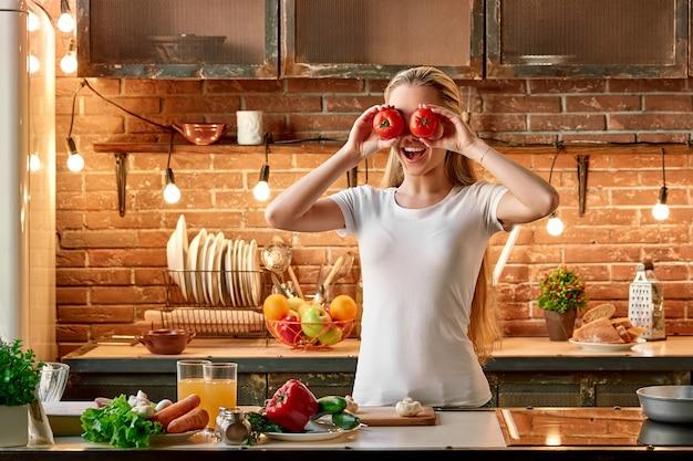 幸せは、モダンなキッチンの居心地の良いインテリアで野菜を調理する幸せな若い女性を調理しています