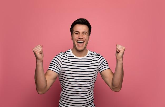 幸せは本物です。拳で手を握りながら笑っている縞模様のtシャツを着た若い男を大喜び。