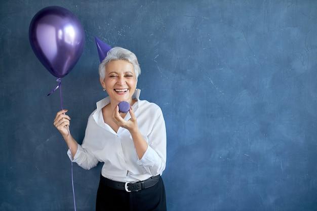 幸福、喜び、レジャー、楽しさとエンターテイメントのコンセプト。誕生日パーティーを楽しんでいる白髪の美しいのんきな引退した女性の肖像画