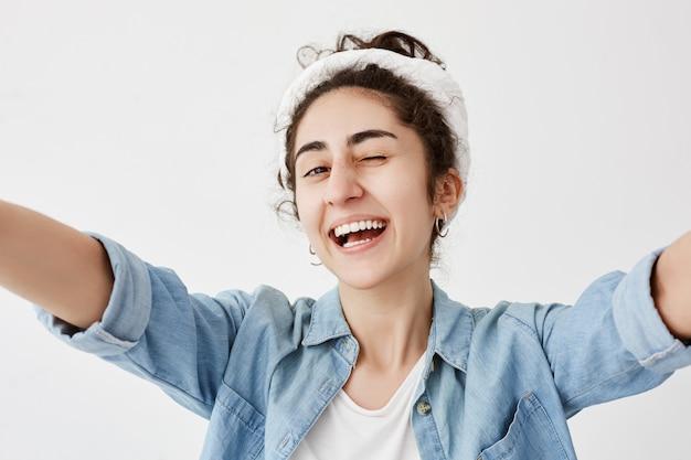 Счастья, радости, молодости. молодая позитивная девушка в джинсовой рубашке над белой футболкой протягивает руки, широко улыбается, моргает, имеет хорошее настроение, демонстрирует белые ровные зубы