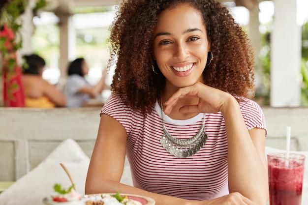 Счастье, досуг, концепция образа жизни. улыбающаяся афроамериканка отдыхает в кафе или ресторане, ест вкусный десерт, пьет коктейль, рада приятному разговору с собеседником.
