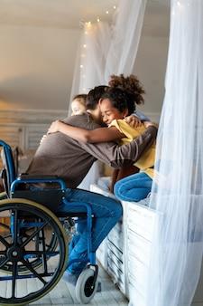 행복 사랑 가족 개념입니다. 집에서 아이들과 포옹하는 휠체어 장애를 가진 웃는 아버지