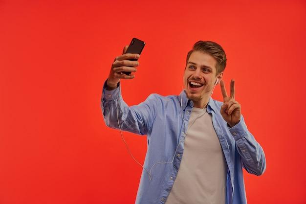 青いシャツを着たヘッドフォンで幸せの男は、平和のシンボルを表示し、電話で写真を撮る