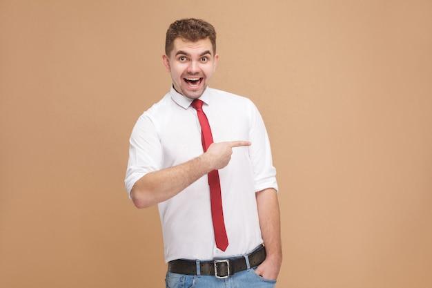 Человек счастья зубастый улыбается и показывает пальцем на пространство для копирования. концепция деловых людей, хорошие и плохие эмоции и чувства. студийный снимок, изолированные на светло-коричневом фоне