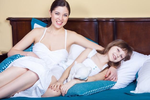 Мама счастья и ее красивая девушка лежат в постели утром, обнимая зубастую улыбку и глядя на