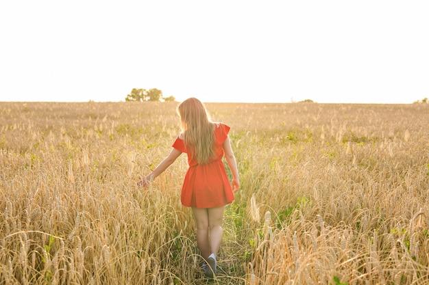 幸福、自然、夏、秋、休暇、そして人々のコンセプト-後ろからフィールドにいる若い女性。