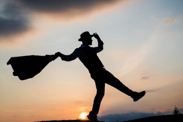 행복은 영감이 필요합니다 남자는 하늘에 에너지 댄서 실루엣으로 가득 찬 동기 부여를 느낍니다.
