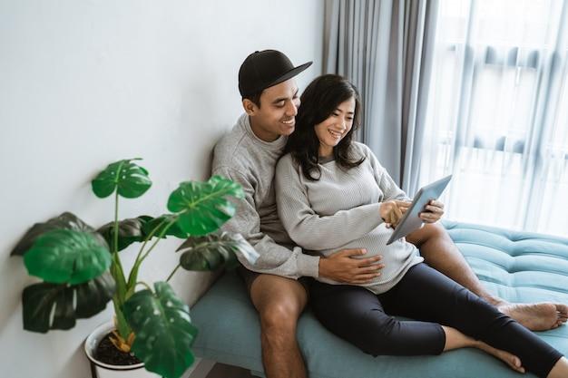 デジタルタブレットを使用しているときに妻の妊娠中の胃を保持しているカップルの幸せ