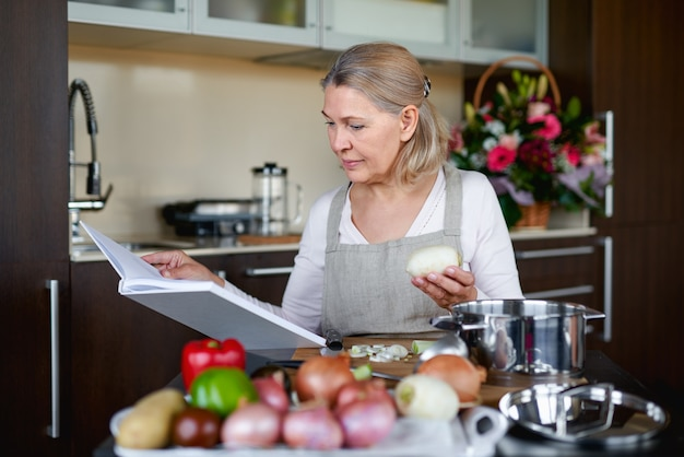 Happiness old woman chooses recipe for pie for whole family