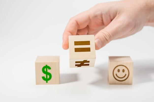 인생의 선택으로서의 행복 또는 돈. 등호에 기호 불균등 변경 손 플립 나무 큐브