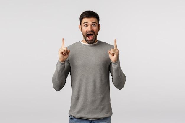 幸福、大喜び、驚きのコンセプト。灰色のセーターを着た驚いた、言葉を失い、不思議なひげを生やした男 Premium写真