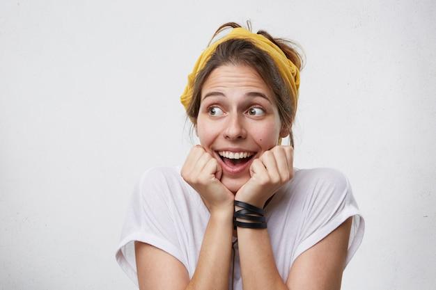 Felicità e concetto di successo. donna eccitata piena di gioia che osserva da parte tenendo le mani sotto il mento tremando di felicità