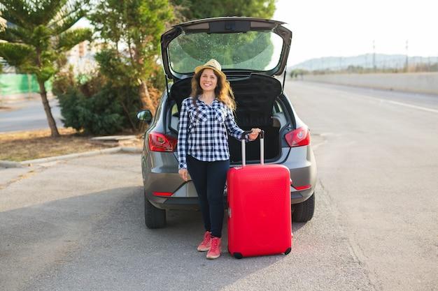 행복, 여행 및 사람들 개념입니다. 웃 고 갈 준비 하는 차 뒤에 서 있는 젊은 여자. 여름 도로 여행입니다.
