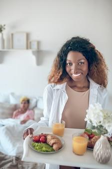 幸福。朝食トレイと花と寝室に立っている白いシャツの明るい笑顔の若いアメリカ人女性