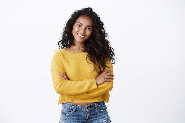 幸福、幸福、自信の概念。陽気な魅力的なアフリカ系アメリカ人の女性の巻き毛のヘアカット、自信を持って強力なポーズで腕を組む胸、決心した笑顔、黄色いセーターを着る