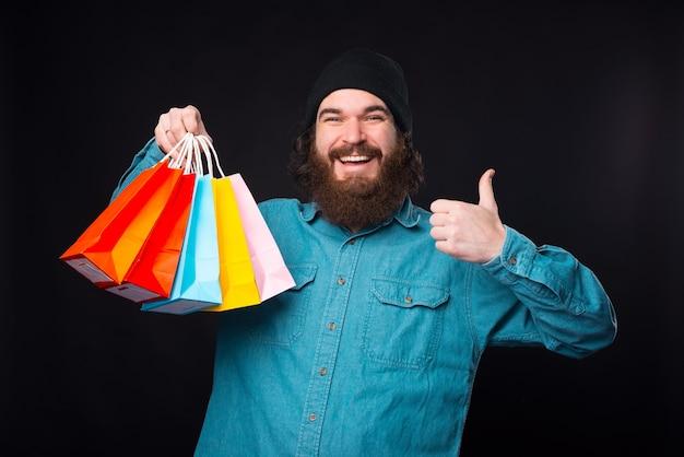 Счастье там, где полные хозяйственные сумки. бородатый мужчина держит некоторые из них, показывая большой палец вверх.