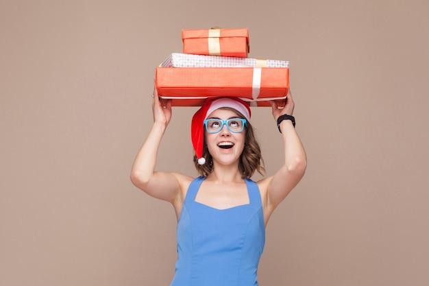 그녀의 머리에 선물 상자를 들고 웃 고 행복 한 여자. 스튜디오 촬영, 갈색 배경